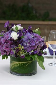 Passion Flowers www.passionflowersdesign.com; Wedding reception centerpiece, with purple Hydrangeas, Sweet Peas, Lisianthus, and Blackberries, with a variegated ginger leaf. Firestone Vineyard