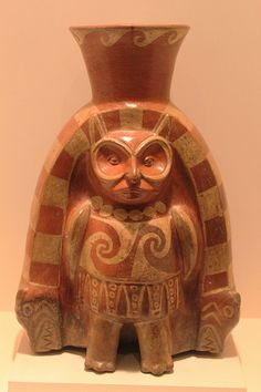 Moche Owl God - The vessel has ears, arms, hands, and a tooth mouth suggest that this creation is not intended to be just an owl but also a humanoid, making it anthropomorphic. This character is prevalent in many depictions of Mochica Art work. He is known as the owl deity, bird priest, bird impersonator, and other names. He is associated with prisoner or human sacrificial ceremonies (Figure 11).  He is depicted commonly holding or receiving a cup of blood or chicha (Bourget and Jones, 266).