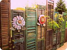 Privacy fence made of assorted old shutters.
