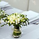 Soft pink, blue, and white hydrangeas and lisianthus are accented with candles in blue and crystal containers.