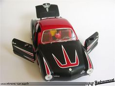 VW Karmann Ghia 1/18 de marque Solido.  Modifs : - Suppression parechocs avant et arrière Lissage global de la carrosserie - Rabaissement - Intérieur velours noir - Volant chaîne - Levier de vitesse démesuré avec tête de diablptin - Carrossage arrière - Moteur avec nouveau filtre à air - Double sorties d'échappement - Peinture carrosserie hot rod 50's noir mat / rouge vif + pinstriping