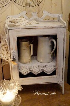 Brocant'elle. Lovely contrast between white items and dark inner cabinet!