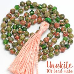 This necklace was hand-knotted using peach cotton thread, 108 6-6.5mm unakite beads and 6mm faceted emerald jade beads, and a wooden guru bead. It measures approximately 31 inches in length with a 2.75-inch tassel. Why hand knot? Because the knots set each gemstone bead apart, showcasing their individual beauty as well as providing a unique style to your necklace. This necklace can be worn as a beautiful fashion accessory or used as a mala. A mala is a string of prayer beads often used…