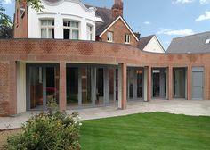 A curved set of cedar bifold doors in Wimbledon
