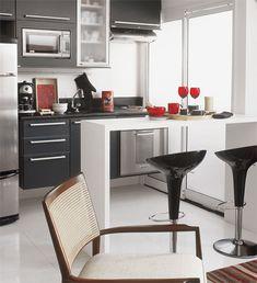 A cozinha, é sutilmente separada da sala por uma bancada de madeira laqueada de branco e acompanhada por banquetas italianas de design contemporâneo.