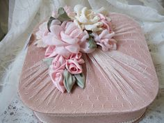 I have an old blue silk quilted hanky box with stains on it....maybe I could cover it with stretch lace and ribbon flowers like this.......?