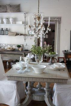 nice little square table..scrolls add pattern chandelier contrast