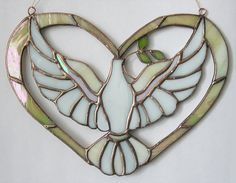 Stained glass suncatcher white dove made in Tiffany style. After dove symbolizing the Holy Spirit. Glass art suncatcher can be hanging on the window.
