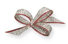AN ELEGANT BELLE EPOQUE DIAMOND AND RUBY BOW BROOCH. Set with old mine and old European-cut diamonds, accented by calibré-cut ruby trim, mounted in platinum and gold (with concealed pendant loops, one small ruby missing), circa 1915