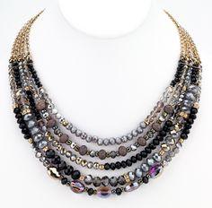 """Multiple strands of faceted glass beads on shiny gold chains creating a lustrous dark gray and black statement necklace. 18"""" long glass/shiny gold metal made in"""
