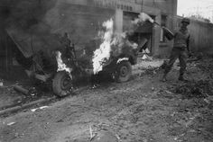 An American soldier attempts to extinguish a burning jeep after the Nazi shelling of Alsdorf, Germany, 1944. [x]