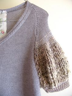nikki gabriel.  Love the play on texture switching up the yarn, but the wire hanger is killing me! lol!