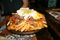 chorrillana -- On a huge plate was piled French fries, beef, sausages, onions and eggs. I shared with three other girls and we managed to finish everything. Carne Asada Fries, Fried Onions, Fried Eggs, Exotic Food, Popular Recipes, Popular Food, French Fries, Love Food, Tasty