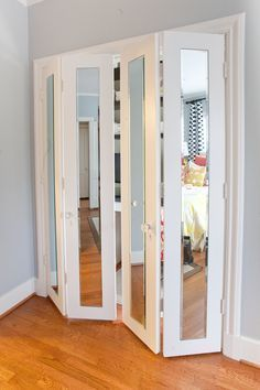 I need to do this... My closet has the same thing toe of doors, but metal... They are so ugly... This would make my room cuter and it would give me mirrors