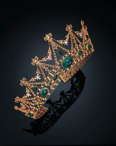 A BELLE EPOQUE EMERALD AND DIAMOND TIARA, TIFFANY CO. designed as a graduated openwork garland and scroll motif gold frame, set with various-shaped cabochon emeralds and pear-shaped emeralds, centering a cushion-shaped double cabochon emerald measuring approximately 17.60 x 14.71 x 10.06 mm, enhanced by diamond collets, mounted in gold, with Austrian assay marks, circa 1905 signed Tiffany Co.