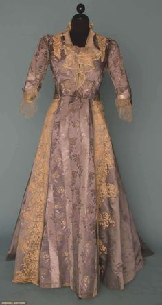 STEELE BLUE SILK & LACE EVENING DRESS, 1880s: 2-piece, fitted bodice & trained skirt, bodice w/ silver lame floral brocade, silk satin skirt, both trimmed w/ cream Brussels mixed lace.