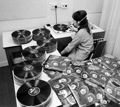 The Quality Control room at EMI pressing plant London England 1965....checking out random copies of The Beatles Rubber Soul LP.