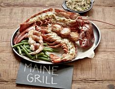 #JoesCrabShack #JoesMaineEvent -  Joe's Crab Shack - The Main Event - Maine Grill: Whole split lobster grilled over an open flame, topped with homemade basil butter and Old Bay® Seasoning paired with bacon wrapped shrimp and wrapped scallops.