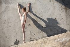 Slim dancer stands in a ballet pose on a gray urban concrete background. Outdoors shooting with sun light.