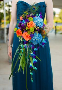 How colorful and fun is this bouquet? We love the idea of incorporating a peacock feather into the mix! // Ben & Molly