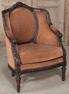 Antique French Louis XVI Armchair. Sculpted for the ultimate comfort from fine French walnut, this bergere features acanthus plumes, rosettes, and laurel bundle motifs, to name a few, carved directly into the solid walnut frame. Oval seatback is flanked by cushy side panels with a generous seat to allow you to relax in comfort.