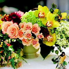 Wedding Centerpiece Mixed Bouquet:   Mixed flowers have been arranged in clusters for this unique centerpiece. Peach roses, hydrangea, zinnias, and yellow orchids have a casual look that would be appealing for a summer wedding.