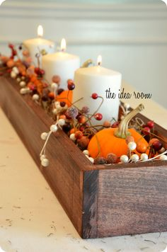 Autumnal Arrangement Tutorial: Cushion candles, pumpkins, and berry garlands with Spanish moss to fashion a simple, beautiful centerpiece.