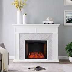Modernize your media room with this white marble fireplace. Herringbone patterned tile and real, Carrara marble join together to craft a look that's both homey and elegant. Glowing faux fire logs add ambiance with flickering LED flames and lifelike embers, with or without heat. Voice-enabled Alexa technology allows for seamless control from anywhere in the room. Add grace and charm to your family living area when you add this real marble fireplace to the h #FlooringInstallation