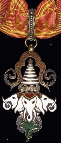 LAOS. Order of the Million Elephants and Parasol, Commander's Neck Badge, Instituted 1844. (Effective date 1920). Silver gilt and enamels, 62 x 38mm. Three white enamel elephant heads and 7-headed serpent under parasol. Cravat loop connects to red moiré ribbon with golden geometric patterns on each margin.
