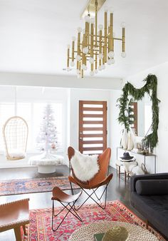Spacious living room with a leather butterfly chair, an Oriental rug, a beautiful golden chandelier and a white Christmas tree.