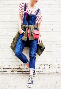 Blair Eadie of Atlantic Pacific wears a striped shirt, overalls, an army jacket, Converse sneakers and a red crossbody bag