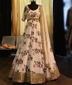 White floral gown with gold border. Lehenga Designs, Kurti Designs Party Wear, Evening Gowns Online, Designer Evening Gowns, Designer Gowns, Designer Party Wear Dresses, Indian Designer Outfits, Indian Gowns Dresses, Pakistani Dresses