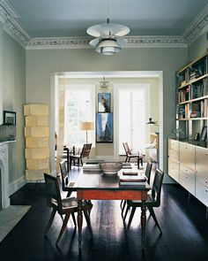 The original back parlor has become the library (foreground), which doubles as a dining room when Gael and Stephen entertain. They ebonized the oak floorboards to anchor the pale walls, but gave the floors a sheen that bounces natural light into the windowless space from the adjoining living room and from a rear studio (background). In the studio, part of a 1930s two-story addition, an ethereal sculpture of Stephen's, a book, is suspended, page by page, on bookbinding thread and glass…