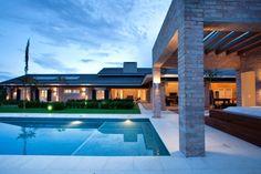A piscina com revestimento em pastilhas 4 cm x 4 cm, Jatobá, e piso em redor da Solarium é ladeada pelo paisagismo assinado por Gilberto Elkis. À direita, a banheira de hidromassagem Jacuzzi. O projeto arquitetônico da casa no interior paulista é de Maurício Karam