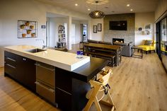 Brodie & Niki Retallick's open plan kitchen, dining and family room with oak flooring throughout. #house #interiordesign #walldecor #blackkitchen #brodieretallick #generationhomes