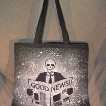 """Good news"" splatter/ spray print bag. Design is painted in white on one side only. Perfect for conventions, trips to the comic shop, as a reusable shopping bag or as a purse.  Black 100% cotton canvas promo bag (thinner than reg. canvas bags from the craft store), Self fabric handles, L 16 inc..."