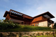 Piscina e integração com a natureza são destaques em casa revestida por madeira