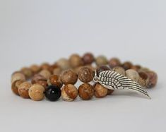 Picture Jasper and Rainbow Obsidian elastic gemstone bracelet set. Accented with an angel wing charm, these gemstones are believed to help ground the wearer and provide courage. Gemstone Bracelets, Bracelet Set, Gemstone Jewelry, Jasper, Gemstones, Rainbow, Angel, Food, Rain Bow