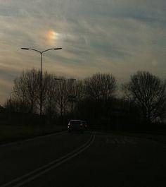 Vlek regenboog bij zonsondergang.
