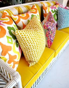 White rattan sofa upholstered in yellow with white piping--and loaded with colorful pillows.