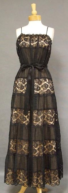 A stunning 1950's evening gown in alternating panels of black pin tucked cotton and black cotton lace. Slightly bloused bodice with spaghetti straps. Dress has a long, gorgeous skirt with a little bit of fullness. Fully lined in a pale peachy pink acetate. Dress has a long black satin ribbon belt (not sure if it is original, but it was with the dress). Rear metal zipper.