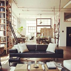 Minimalistic, clean, inviting and masculine. What more do you need out of a wide open loft space?  #loftspace #interiordesign #leathersofa #bookshelves #masculinedesign #midcenturyfurniture