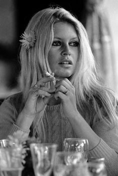 Brigitte Bardot in a sweater, with a flower in her hair.