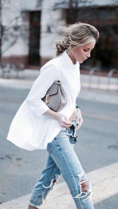 Distressed jeans don't have to be casual. Try pairing them with a crisp blouse, classic bag and romantic hairstyle.