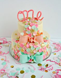 """Elise's first birthday cake, fit for a princess! A confetti themed 2 tier cake, 10 inch and 6 inch rounds, the 6 inch top tier is to be used as Elise's smash cake! From the glittery candy clay confetti and the cursive """"One"""" topper it's all edible! All homemade buttercream and candy clay!  This wonderful pic and table decoration was by Abbey DeHart, check out her blog at http://thecardswedrew.com/   My facebook page for my cakes is www.facebook.com/angelas.cakes2011"""