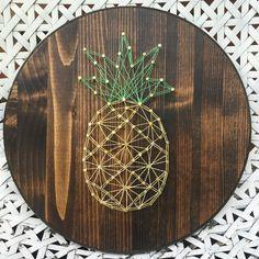 joli objet décoratif fait main avec un gabarit fil tendu à design ananas jaune et vert sur une planche de bois ronde