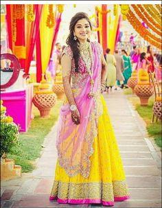 Indian bridal mehndi look. Indian bride wearing bridal lehenga and jewelry…