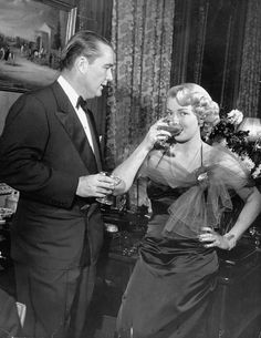 """Thrice- married socialite/heir Henry """"Bob"""" Topping enjoying champagne w.  his latest amorous fixation, actress Lana Turner who is truly gulping down  the """"bu..."""