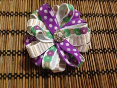 """3/4"""" printed grosgrain ribbon loopy layered flower with gem. Attached to an alligator clip"""