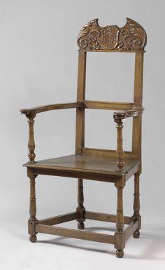 Anonymous | Armchair of a guild of Saint George, Anonymous, c. 1550 - c. 1599 | Armstoel van notenhout. Het meubel rust op slanke vaasvormige poten die onderaan door rechthoekige sporten verbonden worden. De platte armleggers zijn geschulpt en eindigen in voluten. De open rug heeft een onderregel en een dwarsregel. Als bekroning dient een los opgezette, gestoken versiering in de vorm van een gebroken fronton. De versiering bestaat uit acanthusbladeren, peulvruchten en een aan een lint…